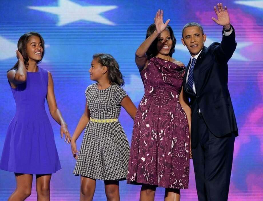 President Barack Obama and First lady Michelle Obama waves to delegates as their daughters Malia and Sasha join them at the Democratic National Convention in Charlotte, N.C., on Thursday, Sept. 6, 2012. (AP Photo/J. Scott Applewhite) / AP