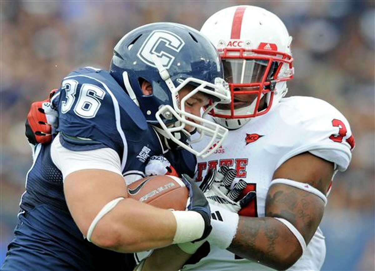 Connecticut's Michael Osiecki, left, is tackled by North Carolina State's Ricky Dowdy during the first half of their football game in East Hartford, Conn., on Saturday, Sept. 8, 2012. (AP Photo/Fred Beckham)