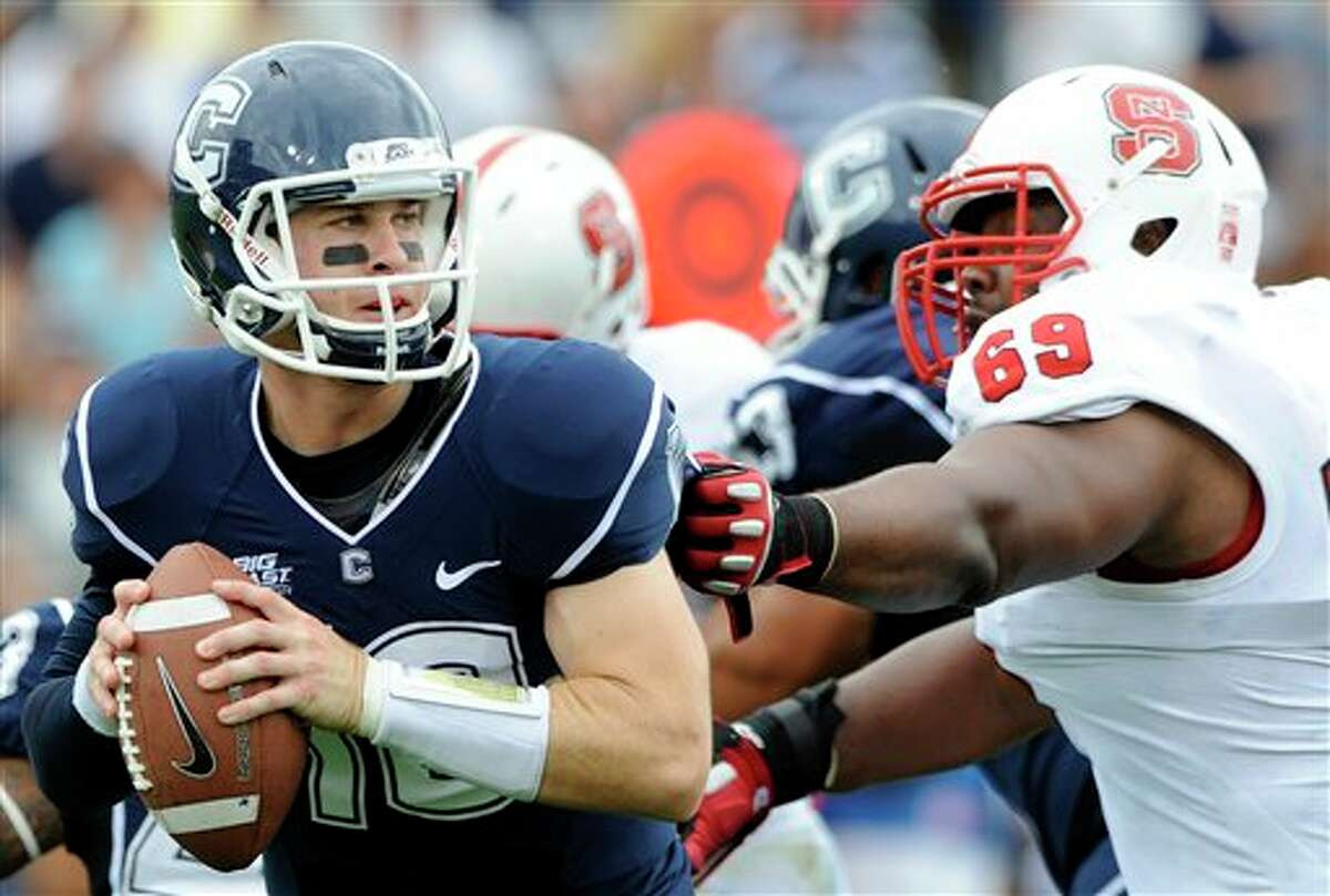 Connecticut's Chandler Whitmer, left, is pressured by North Carolina State's Thomas Teal during the first half of their football game in East Hartford, Conn., on Saturday, Sept. 8, 2012. (AP Photo/Fred Beckham)