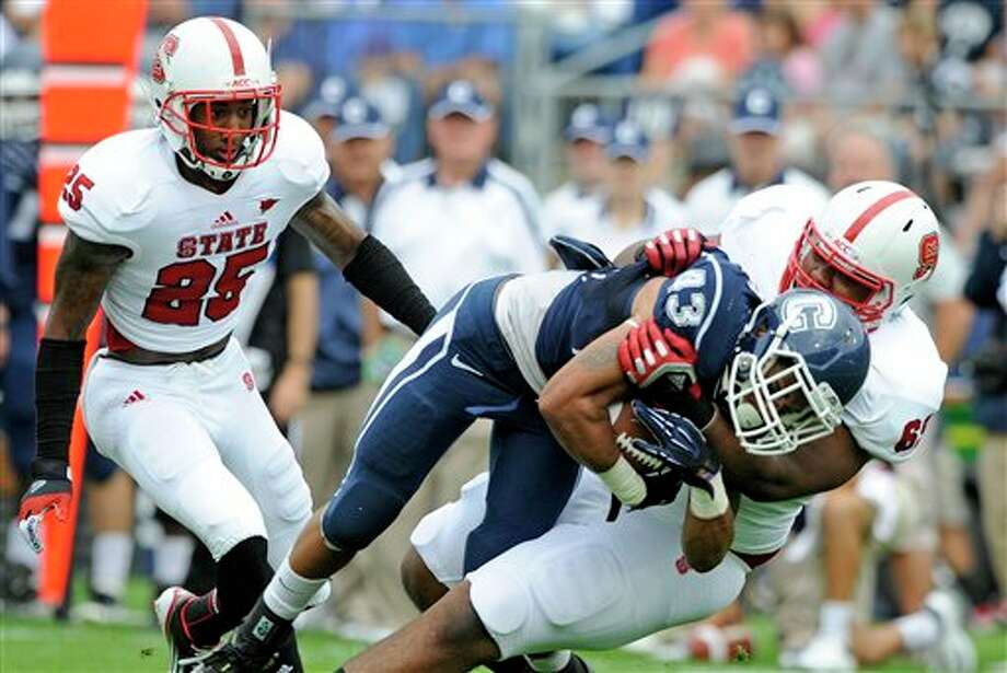 Connecticut's Lyle McCombs (43) is tackled by North Carolina State's Thomas Teal, right, as North Carolina State's Dontae Johnson looks on during the first half of their football game in East Hartford, Conn., on Saturday, Sept. 8, 2012. (AP Photo/Fred Beckham) / FR153656 AP