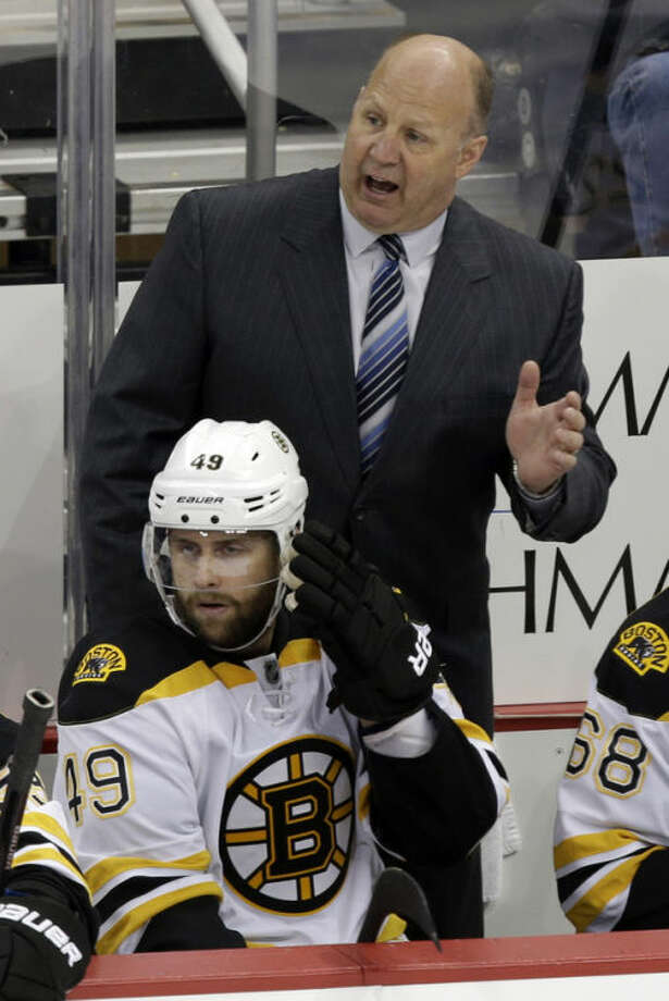Boston Bruins coach Claude Julien stands behind Rich Peverley (49) in the third period of Game 2 of the NHL hockey Stanley Cup playoffs Eastern Conference finals in Pittsburgh Monday, June 3, 2013. The Bruins defeated the Pittsburgh Penguins 6-1. (AP Photo/Gene J. Puskar)