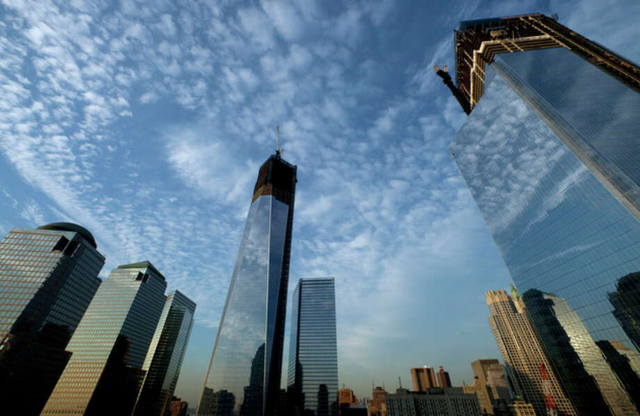 One World Trade Center, center, rises above the National September 11 Memorial and Museum at the World Trade Center, Thursday, Sept. 6, 2012 in New York. Tuesday will mark the eleventh anniversary of the terrorist attacks of Sept. 11, 2001. The World Financial Center is on the left, and Four World Trade Center is at right. (AP Photo/Mark Lennihan) / AP