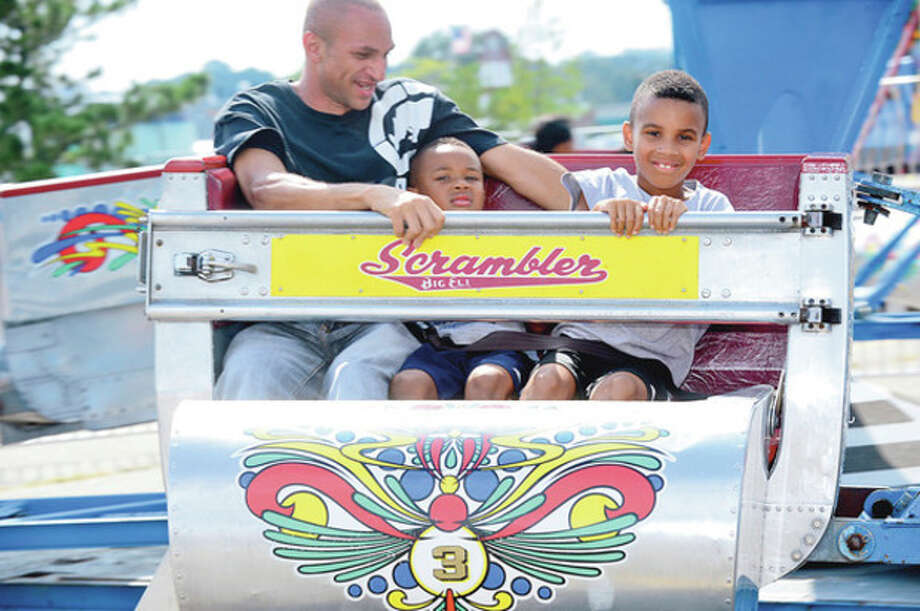 Eddie Gripper takes his nephews, Dillon and Justin Mims on the Scrambler during the Norwalk Seaport Association 2012 Oyster Festival at Veteran's Memorial Park in Norwalk Saturday.Hour photo / Erik Trautmann / (C)2012, The Hour Newspapers, all rights reserved