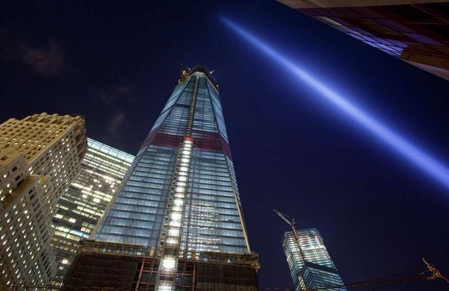 A test of the Tribute in Light shines skyward over One World Trade Center, center, and lower Manhattan, Friday, Sept. 7, 2012 in New York. The tribute will shine the night of Tuesday, Sept. 11 over New York, eleven years after the terrorist attacks. (AP Photo/Mark Lennihan) / AP
