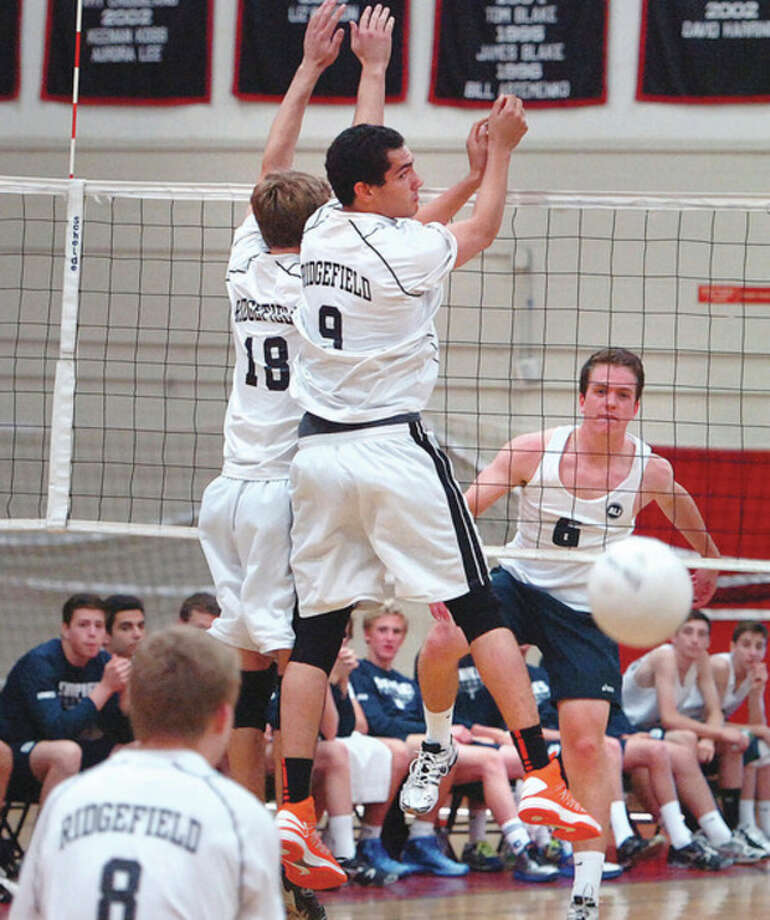 Hour photo/Alex von KleydorffRyan Petyerson of Staples, right, pounds home a point past Ridgefield's Tyler Chittenden (18) and Griffin Jones during Tuesday's CIAC Class L volleyball state semifinal match. A 3-0 win put Staples in Friday's final. / 2013 The Hour Newspapers