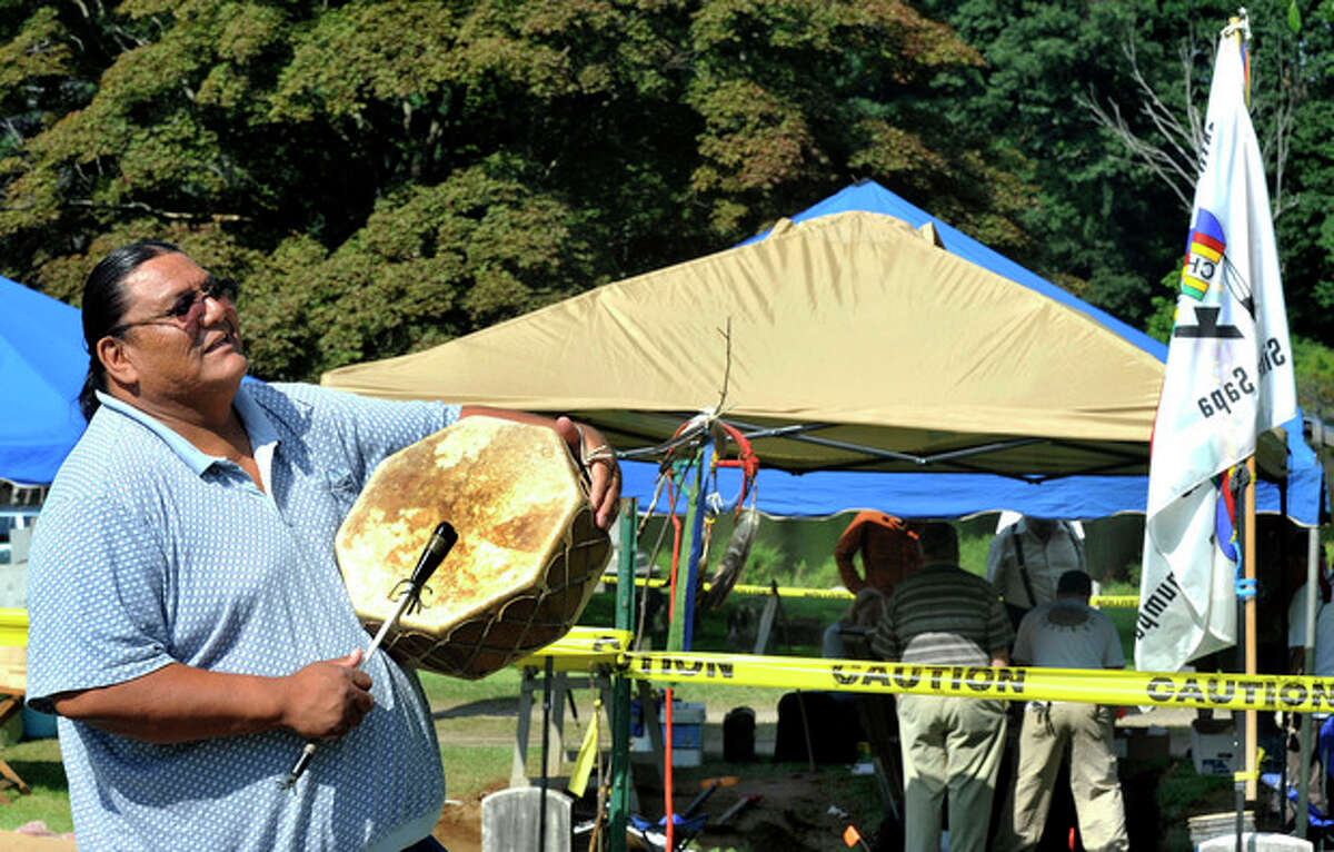 In this Aug. 16, 2012 photo, Richard Red Elk beats a drum during a ceremony near the grave of Albert Afraid of Hawk in Wooster Cemetery, in Danbury, Conn. More than a century after dying from food poisoning while touring New England with Buffalo Bill's Rough Riders, Afraid of Hawk's remains are being returned to South Dakota where he be buried with tribal members. The Oglala Sioux Tribe is planning a traditional Lakota funeral service on the Pine Ridge Indian Reservation on Sunday, Sept. 9, 2012. (AP Photo/The News Times, Michael Duffy) MANDATORY CREDIT
