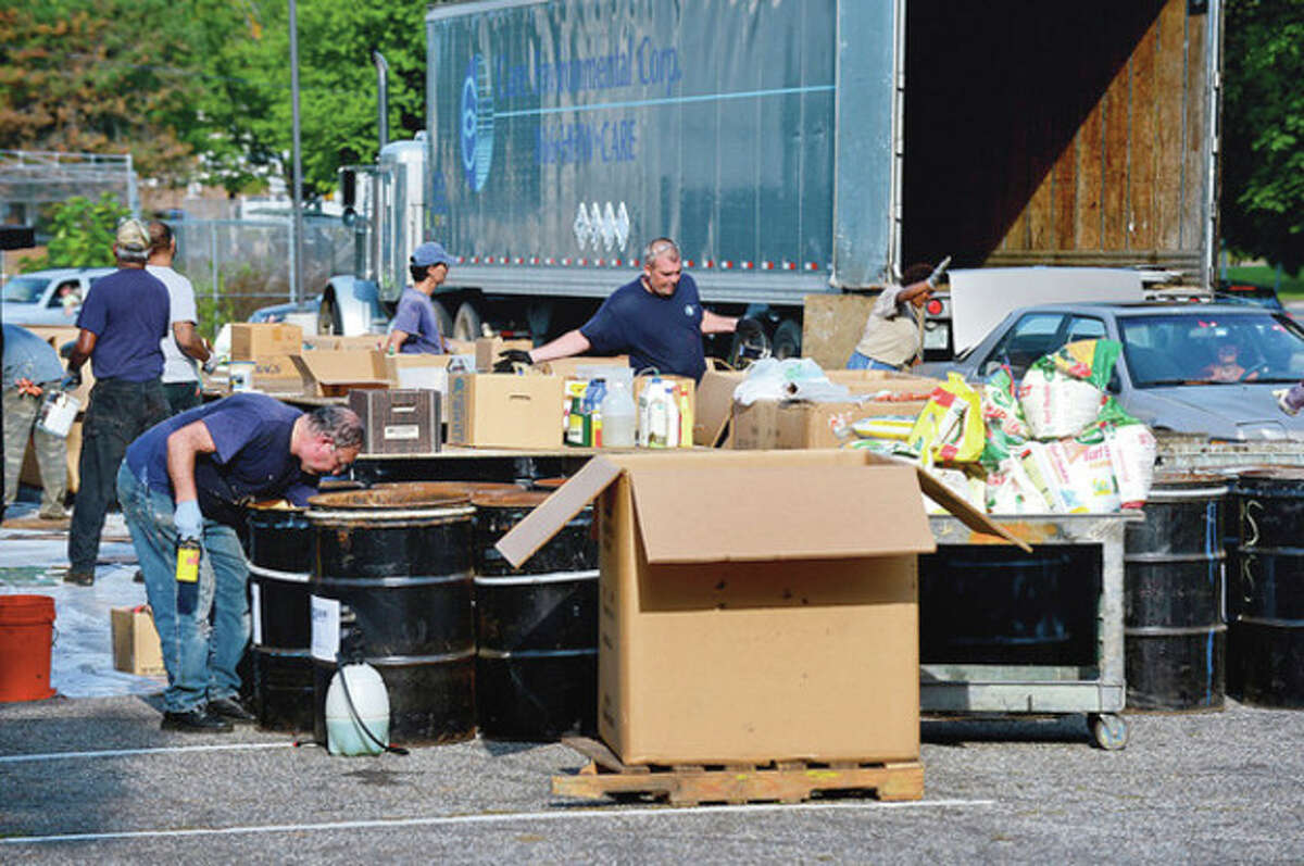 Workers with Care Enviromental Corporation unload hazardous materials for Norwalk residents during the annual collection at Norwalk High School Saturday. Hour photo / Erik Trautmann