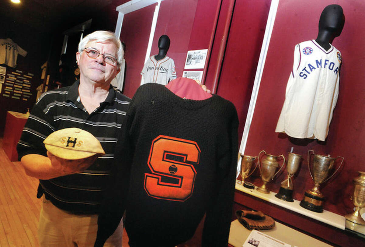 Dan Burke, curator of the sports exhibit at the Stamford Historical Society with a ball cap from Stamford High right fielder Harold H. Mead from 1905 and a 1947 Stamford High baseball letter sweater. photo/Matthew Vinci