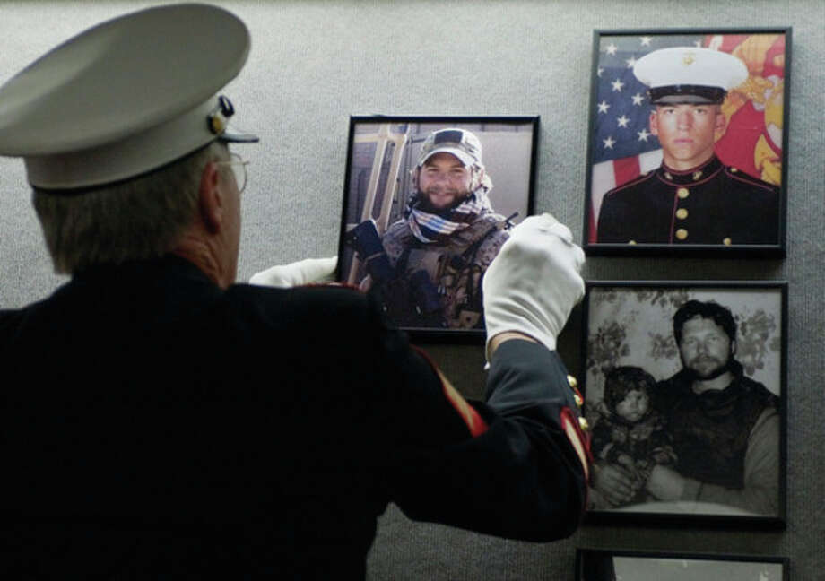 AP photoRet. Marine Sgt. Don Hauser hangs the photograph of Navy SEAL Chief Petty Officer Brian Bill of Stamford on the Connecticut Wall of Honor. / AP2012