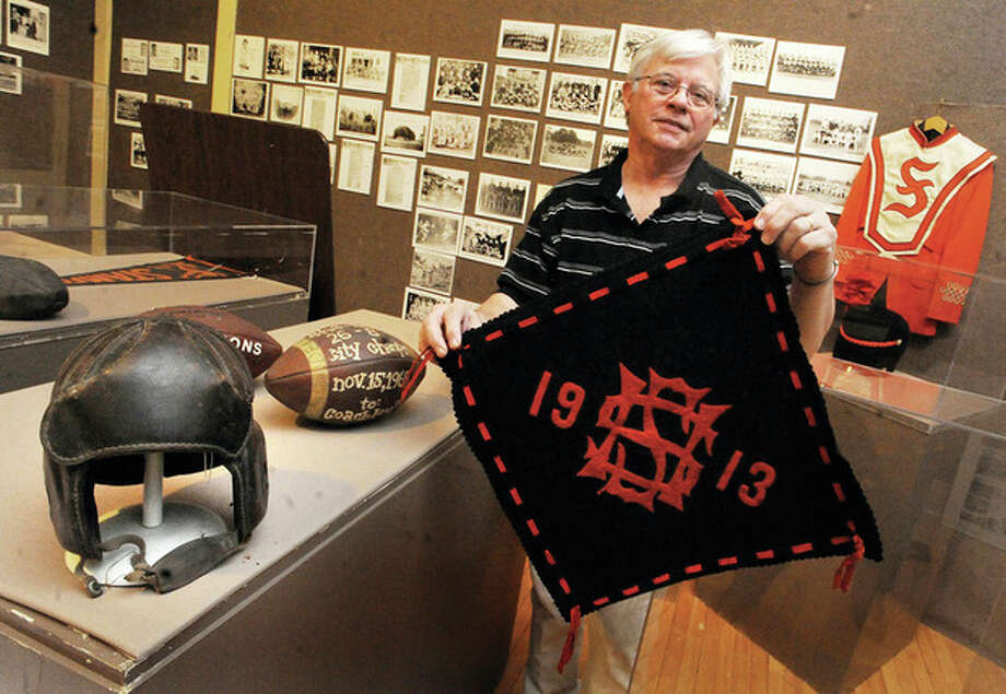 Dan Burke, curator of the sports exhibit at the Stamford Historical Society with 1913 Stamford High banner. On his right is a 1929 leather helmet and a city championship football, Stamford High over Stamford Catholic. photo/Matthew Vinci