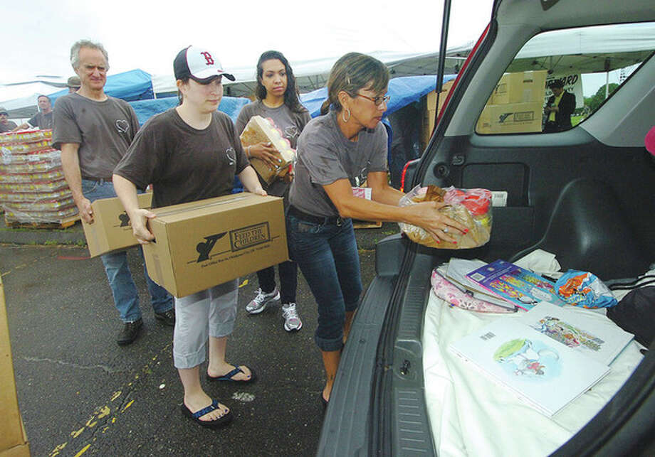 Hour Photo/Alex von Kleydorff . The Salvation Army places jars of Peant Butter and boxes of food on top of coloring books in a families car. The food was distributed to those in need at Veterans park in Norwalk on Monday / 2013 The Hour Newspapers