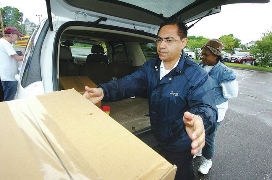 Hour Photo/Alex von Kleydorff Salvation Army Captain Diego Bedoya helps to load boxes of food into the back of a families car, during a food donation to families at Veterans Park in Norwalk. / 2013 The Hour Newspapers