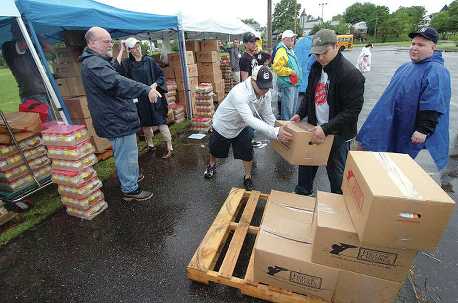 The Salvation Army unloads a pallet of prepared boxes of food for distribution to families at Veterans Memorial Park Monday. / 2013 The Hour Newspapers