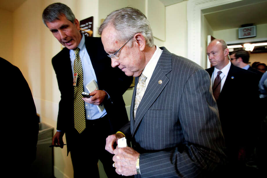 FILE - In this July 12, 2012, file photo Senate Majority Leader Harry Reid of Nevada is pursued by reporters on Capitol Hill in Washington. Fresh off a five-week vacation, lawmakers return to Washington on Monday, Sept. 10, 2012, for a brief pre-election session in which Congress will do what it often does best: punt its problems to the future. At issue is a six-month temporary spending bill to finance the day-to-day operations of the federal government. (AP Photo/Jacquelyn Martin, File) / AP