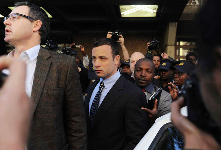 Oscar Pistorius, center, leaves the magistrates court in Pretoria, South Africa, Tuesday June 4, 2013. Pistorius is accused of the shooting death of his girlfriend Reeva Steenkamp on Valentine's Day, Feb 14. The case has been postponed until Aug. 19. Pistorius is back in the glare of public scrutiny for the first time in months, launching the next chapter of a sensational case that transformed the double-amputee Olympian from a smiling global inspiration to a sobbing suspect facing a life sentence in prison if convicted of killing his girlfriend. (AP Photo) / AP
