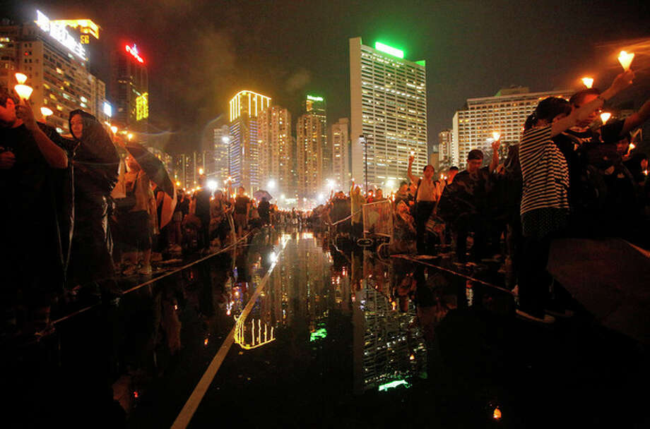 Tens of thousands of people attend a candlelight vigil under heavy rain at Hong Kong's Victoria Park in Hong Kong Tuesday June 4, 2013 to mark the 24th anniversary of the June 4th Chinese military crackdown on the pro-democracy movement in Beijing. (AP Photo/Vincent Yu) / AP
