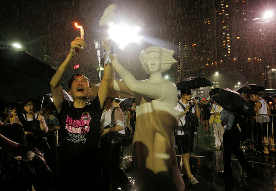 A man holds candlelight in front of a replica of the Goddess of Democracy as tens of thousands of people attend a candlelight vigil under heavy rain at Victoria Park in Hong Kong Tuesday June 4, 2013 to mark the 24th anniversary of the June 4th Chinese military crackdown on the pro-democracy movement in Beijing. (AP Photo/Vincent Yu) / AP
