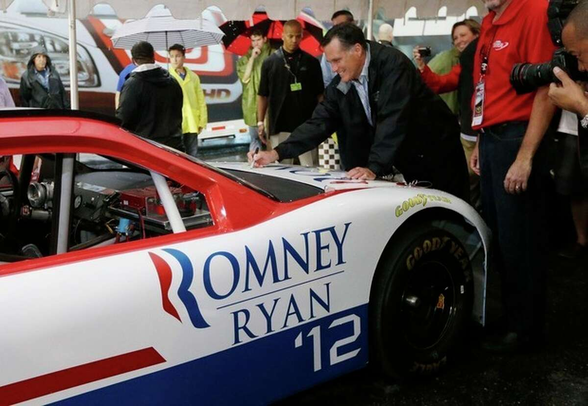 Republican presidential candidate Mitt Romney autographs a vehicle as he campaigns at the Federated Auto Parts 400 NASCAR Sprint Cup Series race at Richmond International Raceway in Richmond, Va., Saturday, Sept. 8, 2012. (AP Photo/Charles Dharapak)