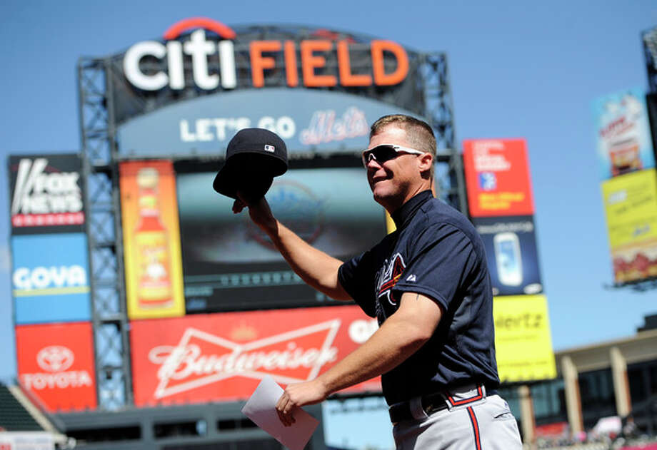 Atlanta Braves third baseman Chipper Jones waves his hat to the cheers of fans as he runs back to the dugout after bringing the lineup card to the umpires before a baseball game against the New York Mets, Sunday, Sept. 9, 2012, at Citi Field in New York. Jones is retiring after the season and it was his last game at Citi Field. (AP Photo/Kathy Kmonicek) / FR170189 AP