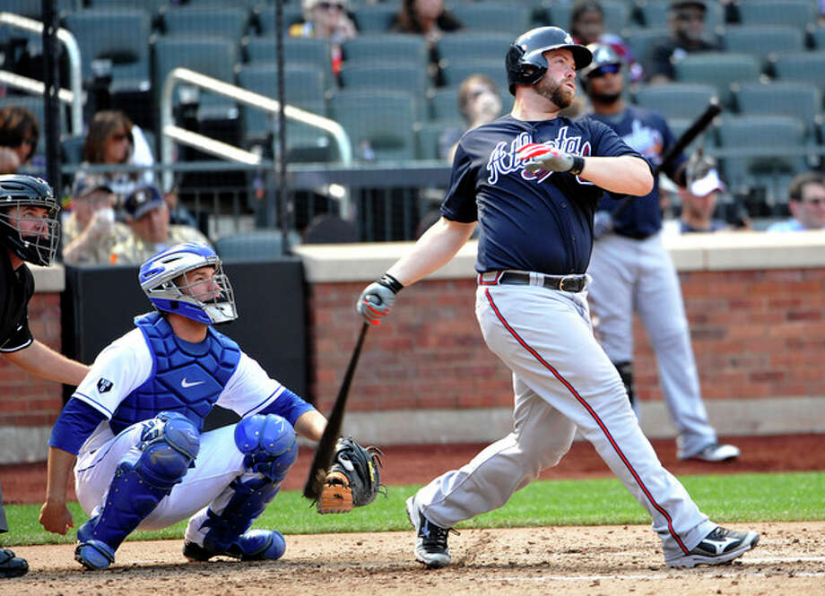 New York Mets catcher Josh Thole, second from left, watches Atlanta Brave's Brian McCann, right, hit a solo home run off Mets' Chris Young in the sixth inning of a baseball game on Sunday, Sept. 9, 2012, at Citi Field in New York. (AP Photo/Kathy Kmonicek) / FR170189 AP