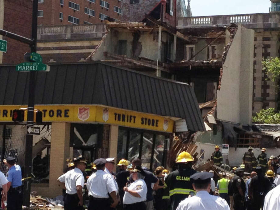 Emergency personnel respond to a building collapse in downtown Philadelphia, where the city fire commissioner says as many as eight to 10 people are believed trapped in the rubble, Wednesday, June 5, 2013. (AP Photo/Jacqueline Larma)