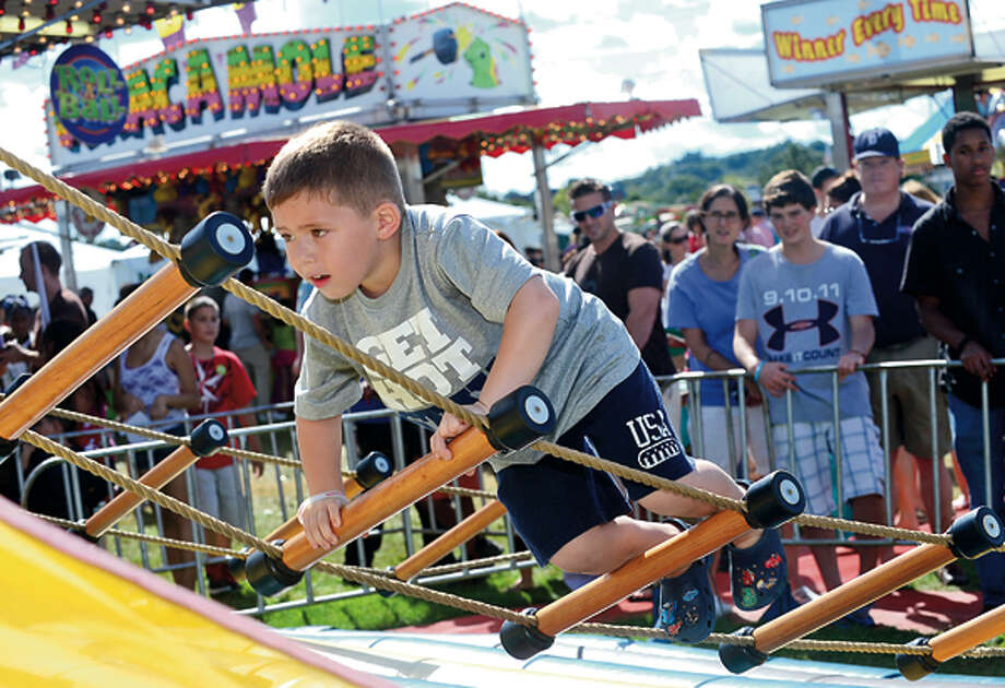 Nicholas Monteiro, 4,tries the rope ladder at the 35th annual Oyster Festival at Veteran's Memorial Park Sunday. Hour photo / Erik Trautmann / (C)2012, The Hour Newspapers, all rights reserved