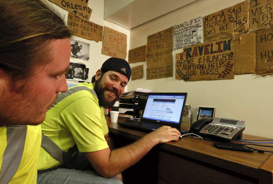 With walls covered in signs from homeless people they have helped, outreach workers Travers Kurr, left, and Mike Miller look over landlord statistics on a laptop in their basement office on April 23, 2013. Landlord Fred Morgan waved off concerns about the condition of the house he rents; saying he is in the process of renovating the property and that he has never been cited by the city for building code violations. However, the Urquhart property has been deemed legally blighted five times in judgments dating to 1994, according to the city's blight status website. (AP Photo/The Times-Picayune, Ted Jackson) MAGS OUT; NO SALES; USA TODAY OUT; THE BATON ROUGE ADVOCATE OUT