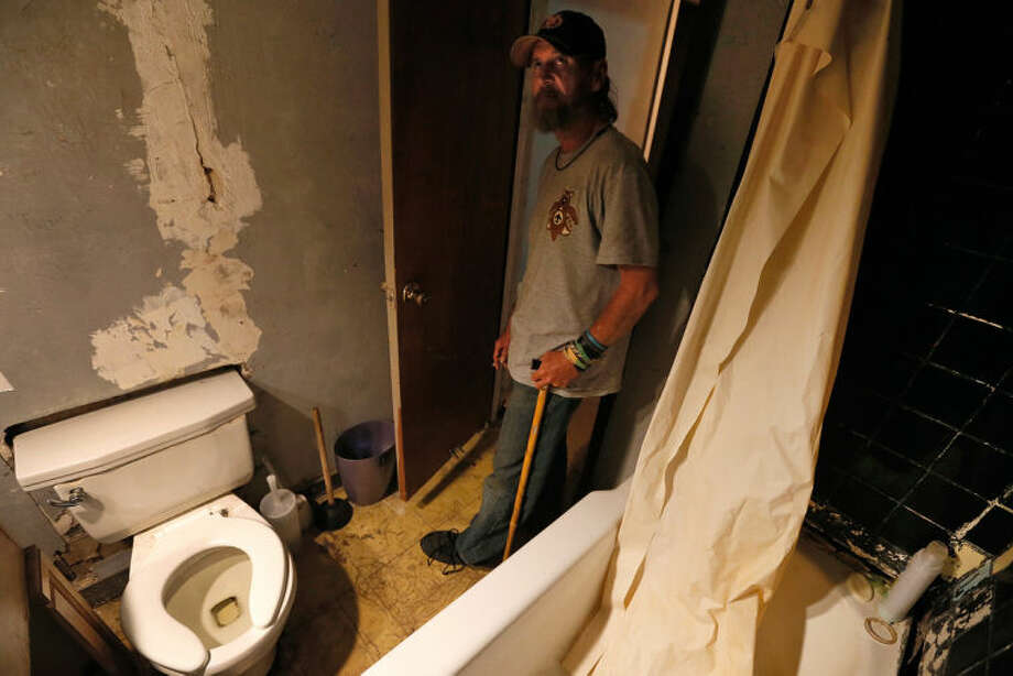 Chuck Manis shows off the bathroom down the hall from the room he and his wife rent from landlord Fred Morgan on April 24, 2013 in New Orleans. Water streams down the walls from the bathroom above, and the tub has collapsed through the floor below. ÔThe doors are falling apart,Õ he says, Ôand he's not doing anything about it. So, as far as I'm concerned, he's a slumlord.Õ (AP Photo/The Times-Picayune, Ted Jackson) MAGS OUT; NO SALES; USA TODAY OUT; THE BATON ROUGE ADVOCATE OUT