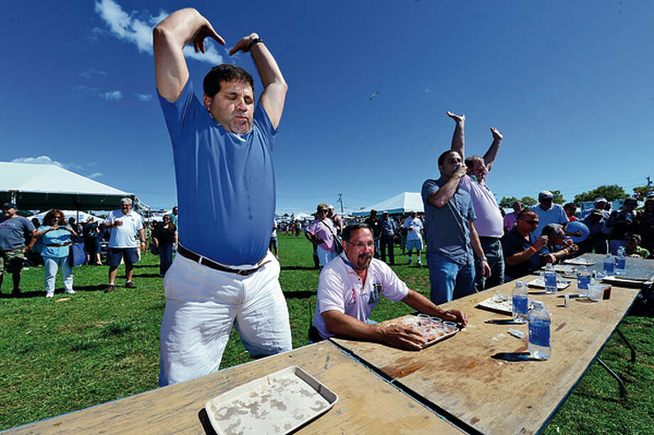 Brien McMahon High School Athletic Director Joe Madaffari finishes the Oyster Slurping Contest at the 35th annual Oyster Festival at Veteran's Memorial Park Sunday. Hour photo / Erik Trautmann / (C)2012, The Hour Newspapers, all rights reserved