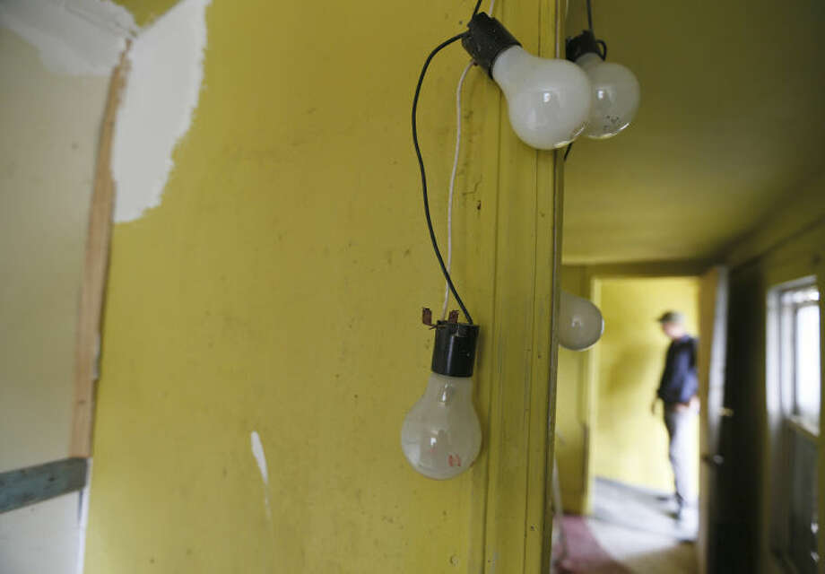 A light fixture hangs from the walls from a home owned by landlord Fred Morgan on April 17, 2013, at Urquhart Street in New Orleans. Tenants get their electricity from a web of extension cords strung from room to room. Morgan waved off concerns about the condition of the house; he said he is in the process of renovating the property and that he has never been cited by the city for building code violations. However, the Urquhart property has been deemed legally blighted five times in judgments dating to 1994, according to the city's blight status website. (AP Photo/The Times-Picayune, Ted Jackson) MAGS OUT; NO SALES; USA TODAY OUT; THE BATON ROUGE ADVOCATE OUT