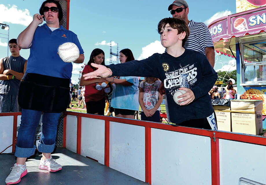 Eoin Mueller, 7, tries the softball toss at the 35th annual Oyster Festival at Veteran's Memorial Park Sunday. Hour photo / Erik Trautmann / (C)2012, The Hour Newspapers, all rights reserved