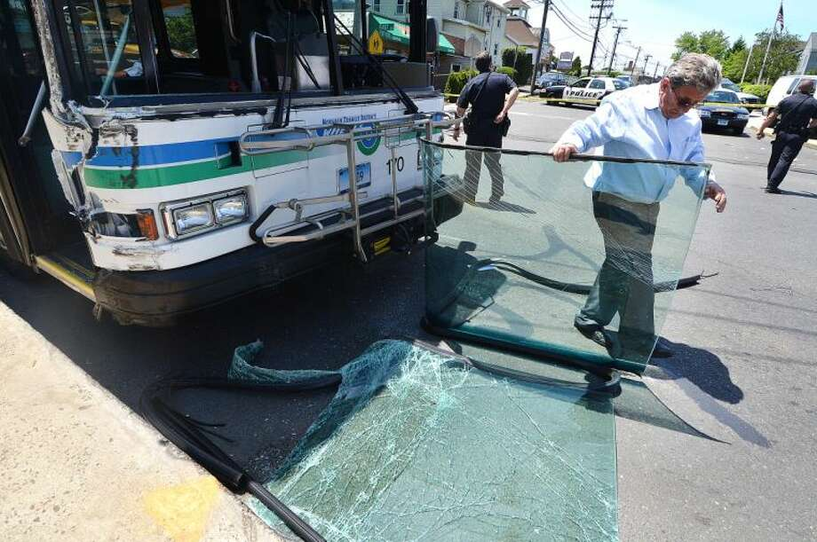 Hour Photo/Alex von Kleydorff Norwalk transit District Director of Operations John Sulaj clears a section of the windshield from in front of the #11 bus that struck a utilty pole on East Ave on Wednesday .
