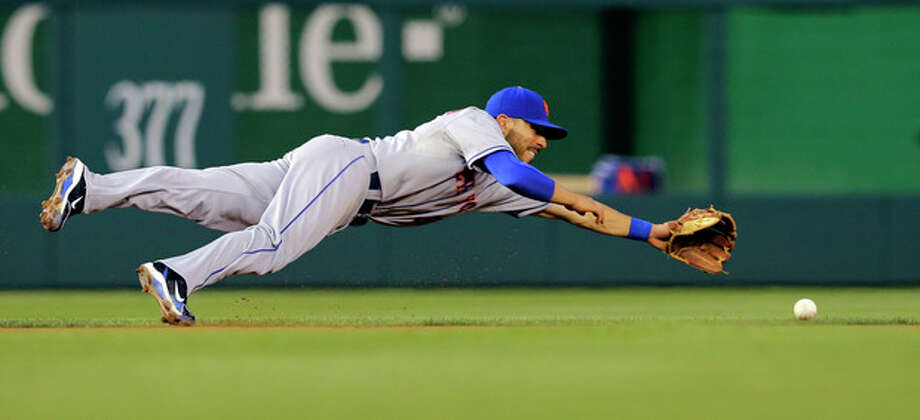 New York Mets shortstop Omar Quintanilla dives but misses a ball hit by Washington Nationals' Kurt Suzuki during the fourth inning of a baseball game at Nationals Park Wednesday, June 5, 2013, in Washington. Suzuki singled on the play. (AP Photo/Alex Brandon) / AP