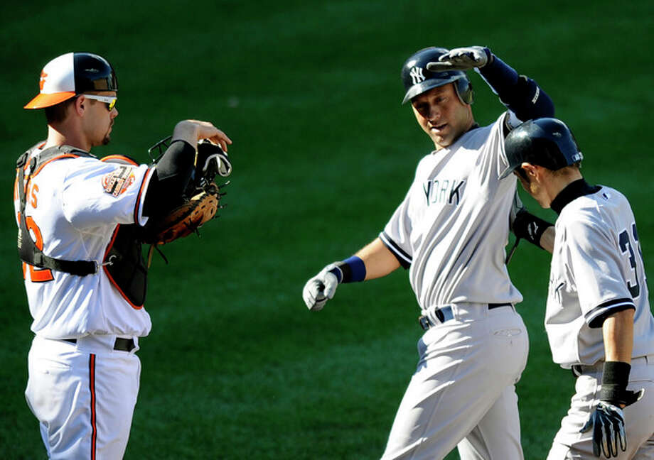 New York Yankees' Derek Jeter, center, celebrates his two-run home run with teammate Ichiro Suzuki, right, of Japan, as Baltimore Orioles catcher Matt Wieters watches at left, during the eighth inning of a baseball game, Sunday, Sept. 9, 2012, in Baltimore. The Yankees won 13-3. (AP Photo/Nick Wass) / FR67404 AP