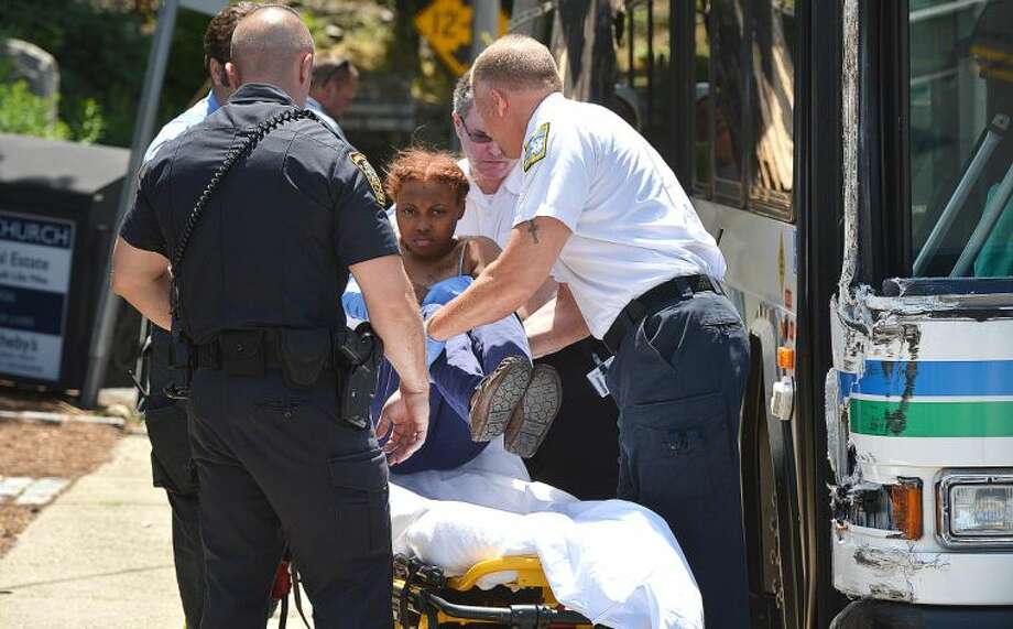 Hour Photo/Alex von Kleydorff A Passenger is removed from a Wheels bus by Norwalk Hospital Paramedics and placed on a stretcher after the bus hit a utility pole on East Ave. Wednesday afternoon