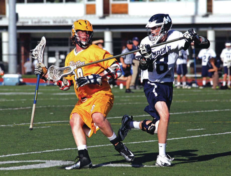 Hour photo/Danielle Robinson CallowayWeston's Alex Crowell, left, tries to keep posession of the ball as he's badgered by a Morgan defender during the Class S semifinal game at Fairfield Ludlowe High School Wednesday afternoon. Weston advanced to Saturday's championship game with a 10-5 victory.