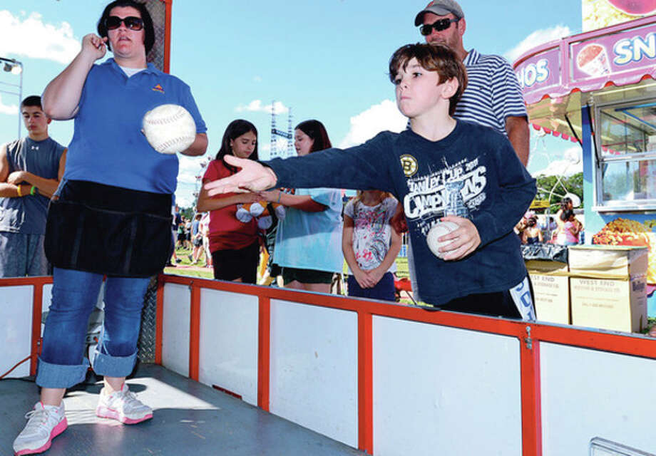 Eoin Mueller, 7, tries the softball toss at the 35th annual Oyster Festival at Veteran's Memorial Park Sunday.Hour photo / Erik Trautmann / (C)2012, The Hour Newspapers, all rights reserved