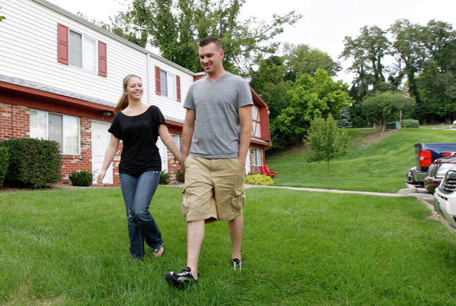 "In this Monday, Aug. 20, 2012 photo, Marine Sgt. Ron Strang, right, walks with his girlfriend, Monica Michna, in the yard by his home in Jefferson Hills, Pa., just south of Pittsburgh. In 2008, the federal government created AFIRM, the Armed Forces Institute of Regenerative Medicine, a network of top hospitals and universities around the country, and gave $300 million in grants to spur new treatments using cell science and advanced plastic surgery. Strang is among those benefiting. The 28-year-old former Marine sergeant from Pittsburgh lost half of his left thigh muscle to shrapnel, leaving too little to stabilize his gait. ""My knee would buckle and I'd fall over,"" he said. Now, after an experimental cell treatment at the University of Pittsburgh Medical Center, ""I'm able to run a little bit"" and play a light football game with friends, he said. ""It's been a huge improvement."" (AP Photo/Keith Srakocic) / AP"