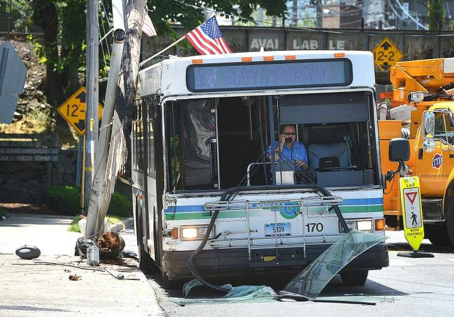 Hour Photo/Alex von Kleydorff . The driver of a #11 Wheels bus communicates over the phone after hitting a utilty pole and snapping it on East Ave and Fort Point St in Norwalk Wednesday afternoon.