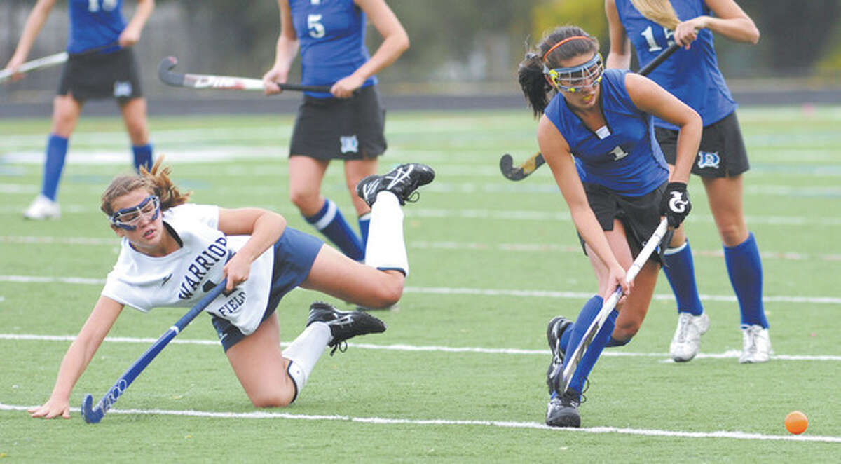 File photo by John Nash Wilton's Madison Hendry, left, goes flying while Darien's Alex Iqbal maintains control of the ball during a game last season. Hendry hits the turf a lot, but always bounces back up.