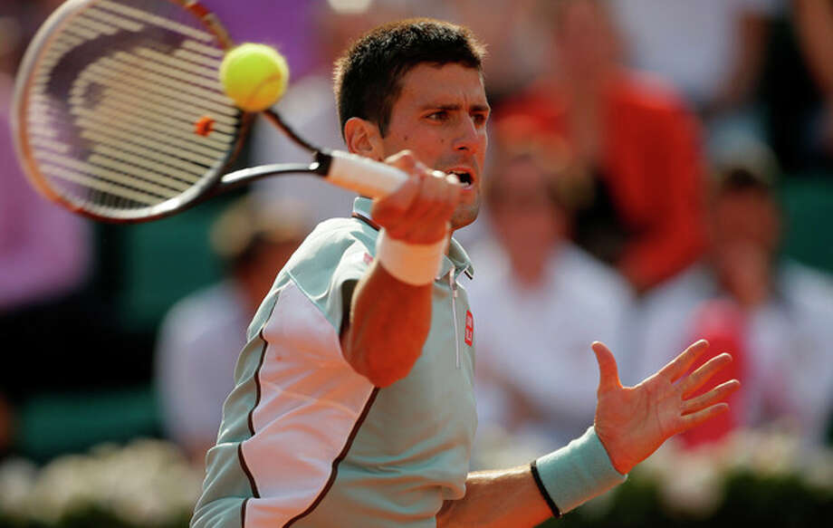Serbia's Novak Djokovic returns the ball to Germany's Tommy Haas during their quarterfinal match of the French Open tennis tournament at the Roland Garros stadium Wednesday, June 5, 2013 in Paris. Djokovic won 6-3, 7-6, 7-5. (AP Photo/Michel Spingler) / AP