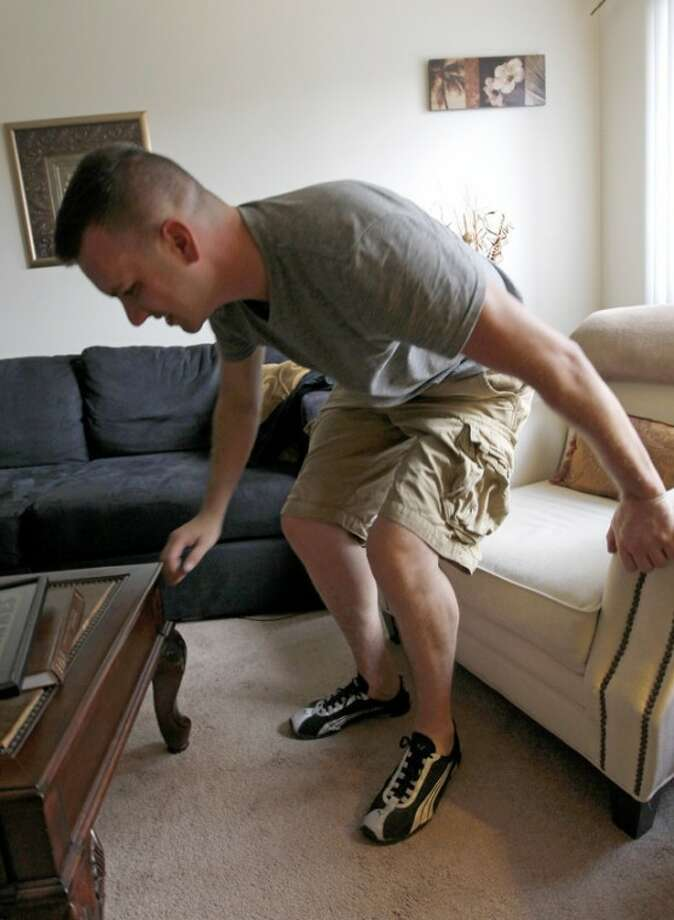 """In this Monday, Aug. 20, 2012 photo, Marine Sgt. Ron Strang gets up from a chair in the living room of his home in Jefferson Hills, Pa. just south of Pittsburgh. He lost half of his left thigh muscle in a bomb blast in Afghanistan and with an experimental implant of connective tissue developed from pigs, it has had it strengthened. """"It's been a huge improvement,"""" he says. (AP Photo/Keith Srakocic)"""