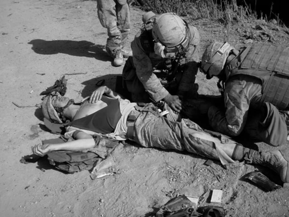 AP photo / Ron StrangIn this April 4, 2010, photo provided by Marine Sgt. Ron Strang, Strang lies on the ground after being hit by shrapnel in a bomb blast in Marja, Afghanistan. / Ron Strang