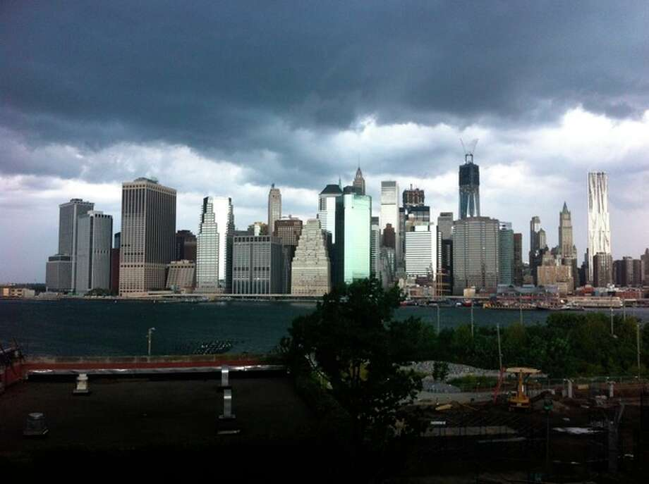 In this photo provided by Gothamist, dark clouds loom over the skyline, Saturday, Sept. 8, 2012, in New York. Two tornadoes struck New York City on Saturday, one swept out of the sea and hit a beachfront neighborhood and the second, stronger twister hit moments later, hurling debris in the air, knocking out power and startling residents who once thought of twisters as a Midwestern phenomenon. (AP Photo/Gothamist, Jake Dobkin) MANDATORY CREDIT / Gothamist