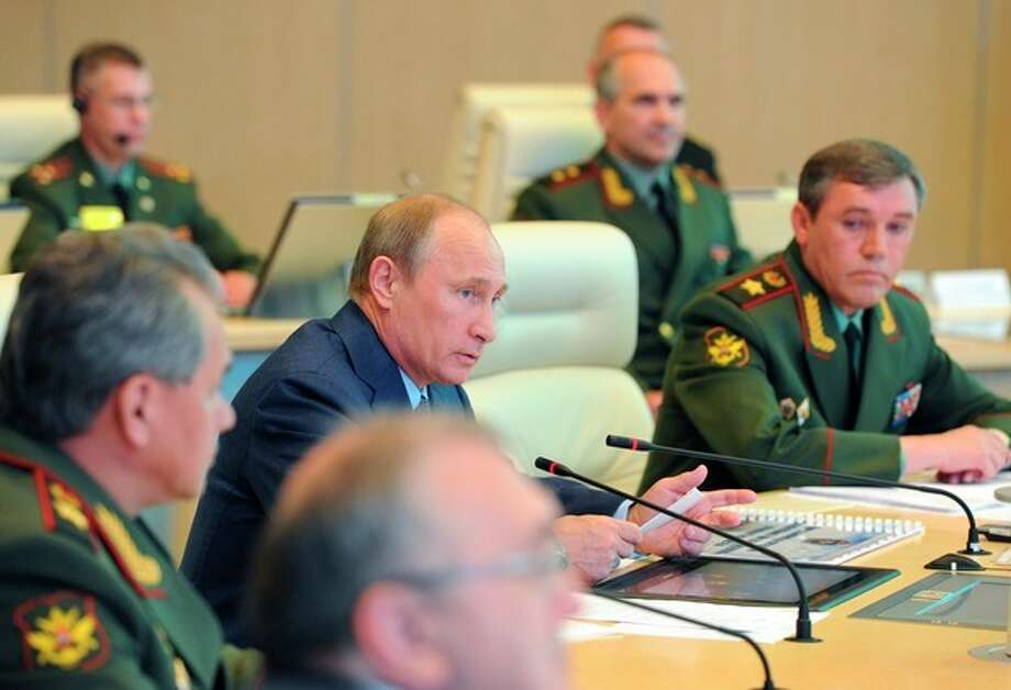 """Russian President Vladimir Putin, second left, has a meeting in the Russian Armed Forces main operational center in Moscow, Russia, Thursday, June 6, 2013. At right is Chief of the armed forces' General Staff Gen. Valery Gerasimov. and at left is Defense Minister Sergei Shoigu. President Vladimir Putin says Russia will permanently keep a navy squadron in the Mediterranean Sea to protect its interests. Speaking at Thursday's meeting with the military brass, Putin said the move shouldn't be interpreted as saber-rattling. He said the Mediterranean is a """"strategically important region, where we have interests connected with ensuring Russia's national security."""" (AP Photo/RIA-Novosti, Mikhail Klimentyev, Presidential Press Service) / RIA Novosti Kremlin"""