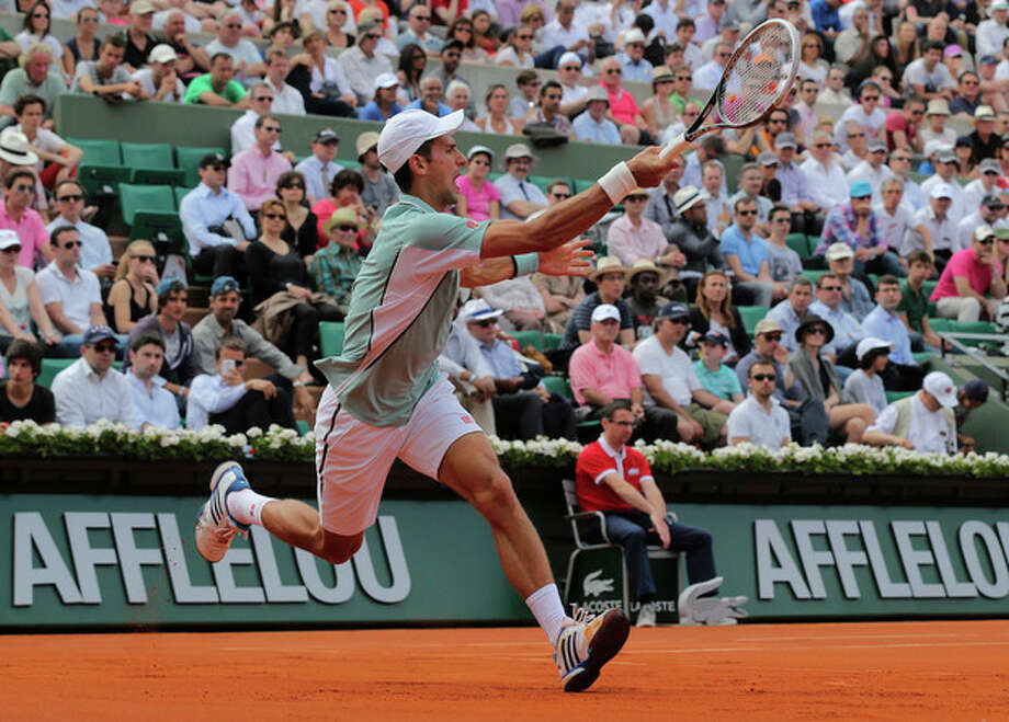 Serbia's Novak Djokovic returns the ball to Germany's Tommy Haas during their quarterfinal match of the French Open tennis tournament at the Roland Garros stadium Wednesday, June 5, 2013 in Paris. (AP Photo/Michel Euler) / AP