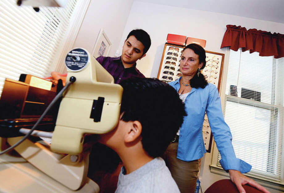 Hour photos / Erik TrautmannUmar Munshi works with Dr. Randy Schulman, owner of The Center for Integrated Vision, 139 Main St., Norwalk, to provide a battery of visual exams for children to screen for possible visual learning disabilities. / (C)2012, The Hour Newspapers, all rights reserved