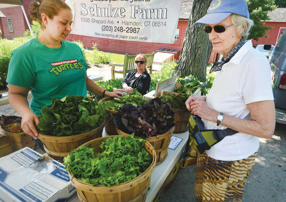 Hour Photo/Alex von Kleydorff Wiltons Amy Quigley shops for fresh produce with help from Michelle Bojarski with Schutze Farm stand at Wiltons Farmers Market on Wednesday