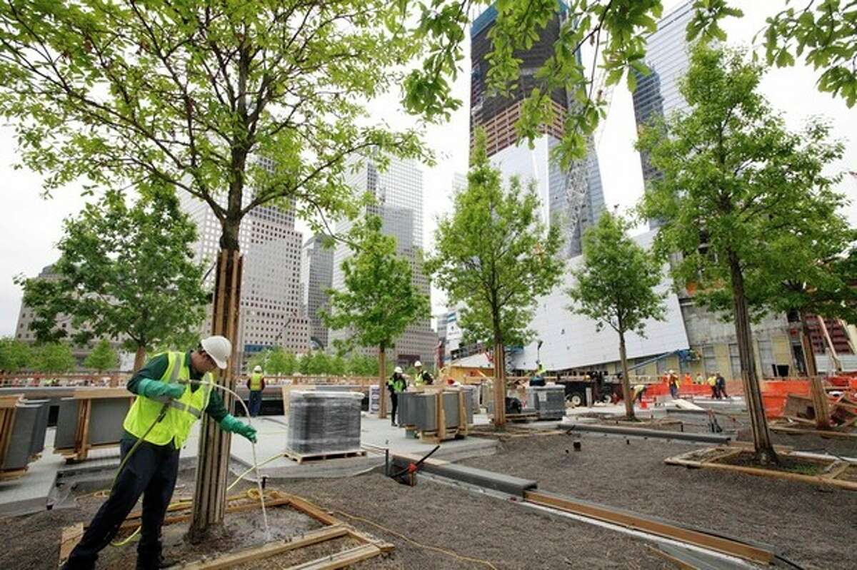 FILE - In this May 13, 2011 file photo, arborist Jeremy DeSimone, left, sprays fertilizer on a swamp white oak at the National September 11 Memorial at the World Trade Center site in New York. The foundation that runs the memorial estimates that once the roughly $700 million project is complete, it will cost $60 million a year to operate. (AP Photo/Mark Lennihan, File)