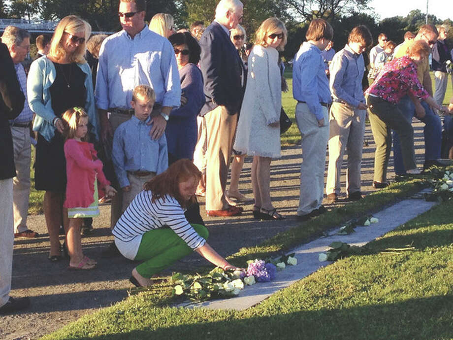 Hour photo / Robin KaminskiEmma Hunt, 12, kneels down and places a single white rose next to the name of her father, William Christopher Hunt, who was killed in the 9/11 terrorist attacks.